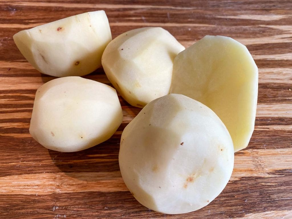 Potatoes on chopping board for making Scottish Tattie Scones Recipe