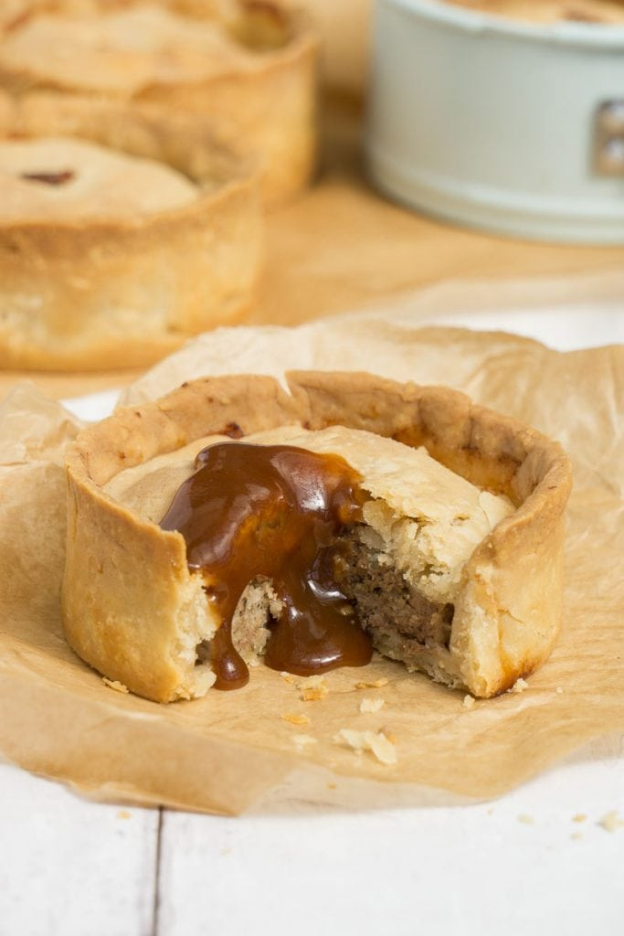 Scotch Pie covered in brown sauce with other scotch pies in the background.