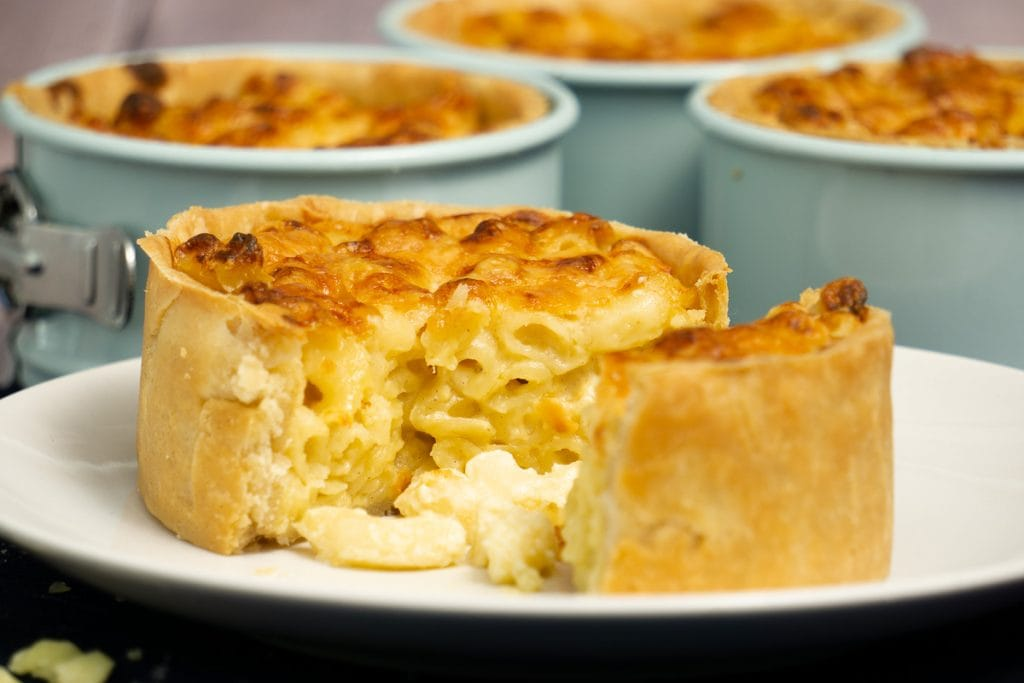 Macaroni Scotch Pie Recipe with pie on plate and tins in background