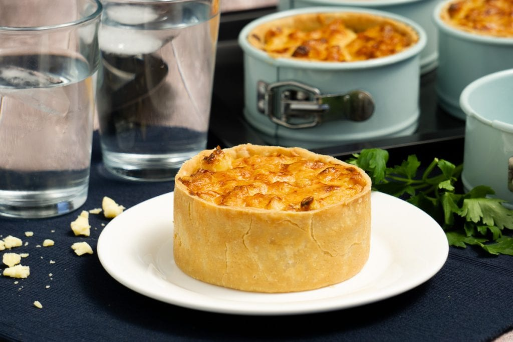 Scottish Macaroni Pie Recipe - Pie on plate with pie tins in background, and glasses of water