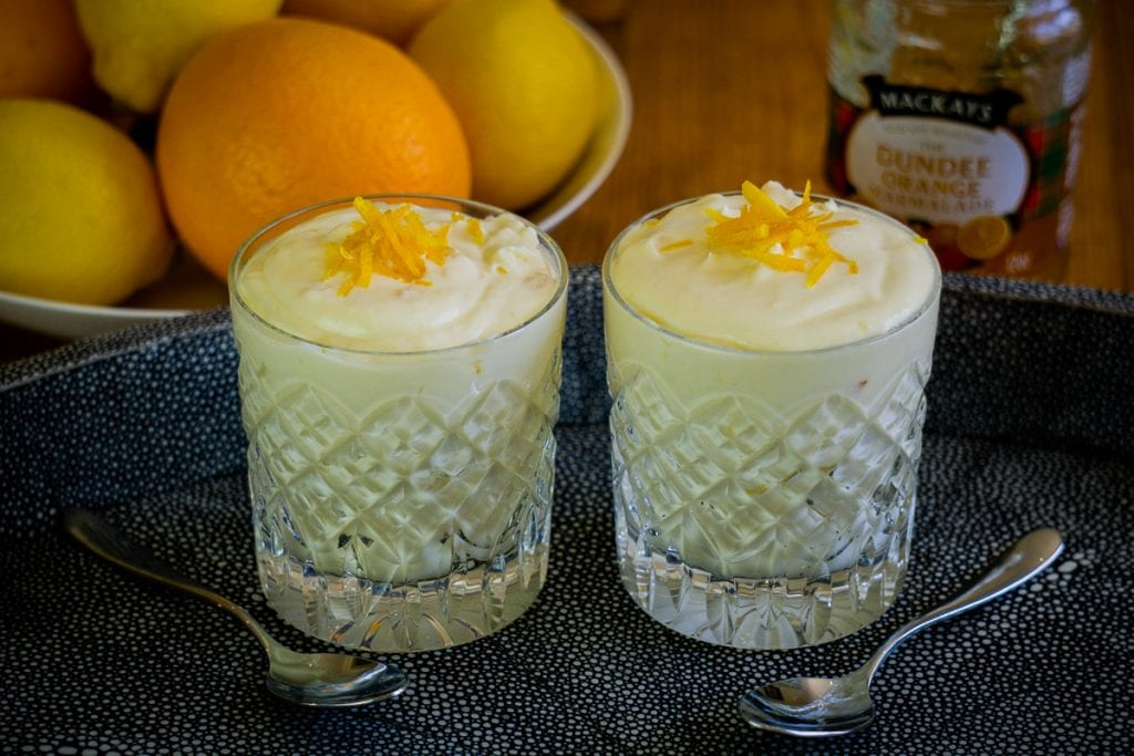 Two glasses of Caledonian Cream on a tray with Dundee Marmalade and oranges