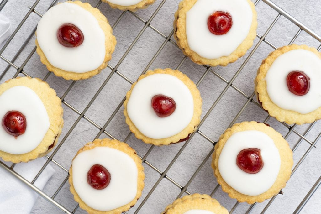 Scottish Double Biscuits - Scottish Iced Biscuits on a cooking rack with a cherry on top