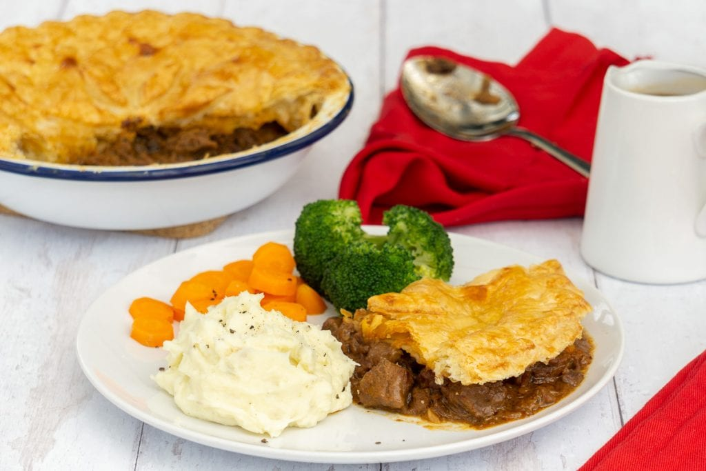 Scottish Steak Pie Recipe in pie dish and on plate with vegetables