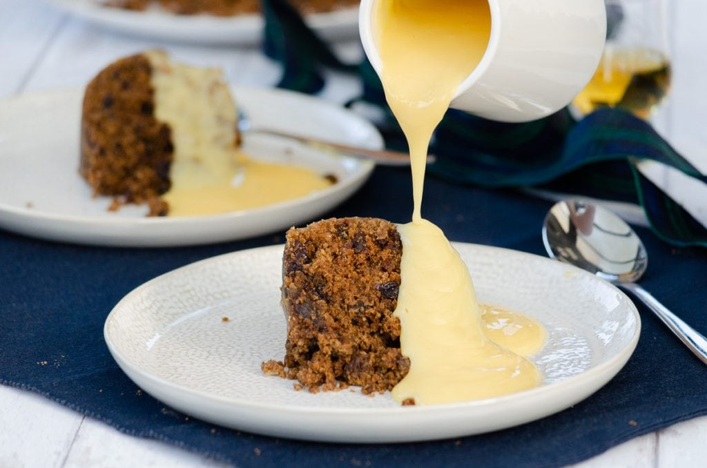 Clootie Dumpling on a plate with a jug of custard being poured over it