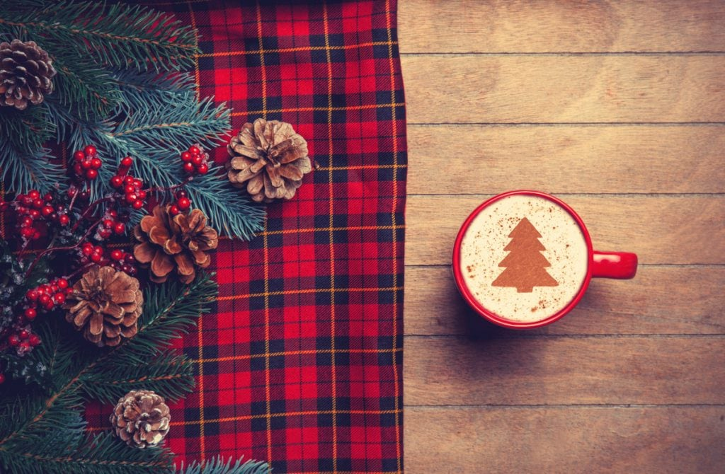 Cappuccino and pine branch with tartan on wooden table. - Scottish Christmas Food Menu Ideas