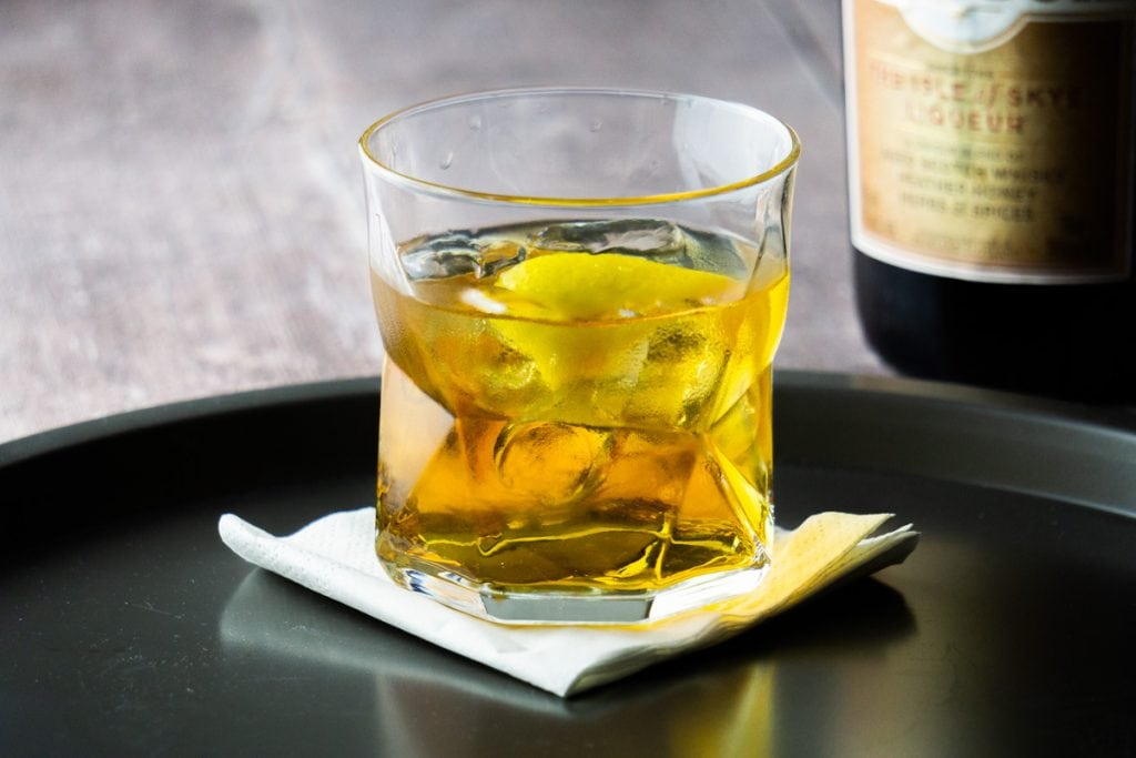 A Rusty Nail cocktail with a twist of lemon