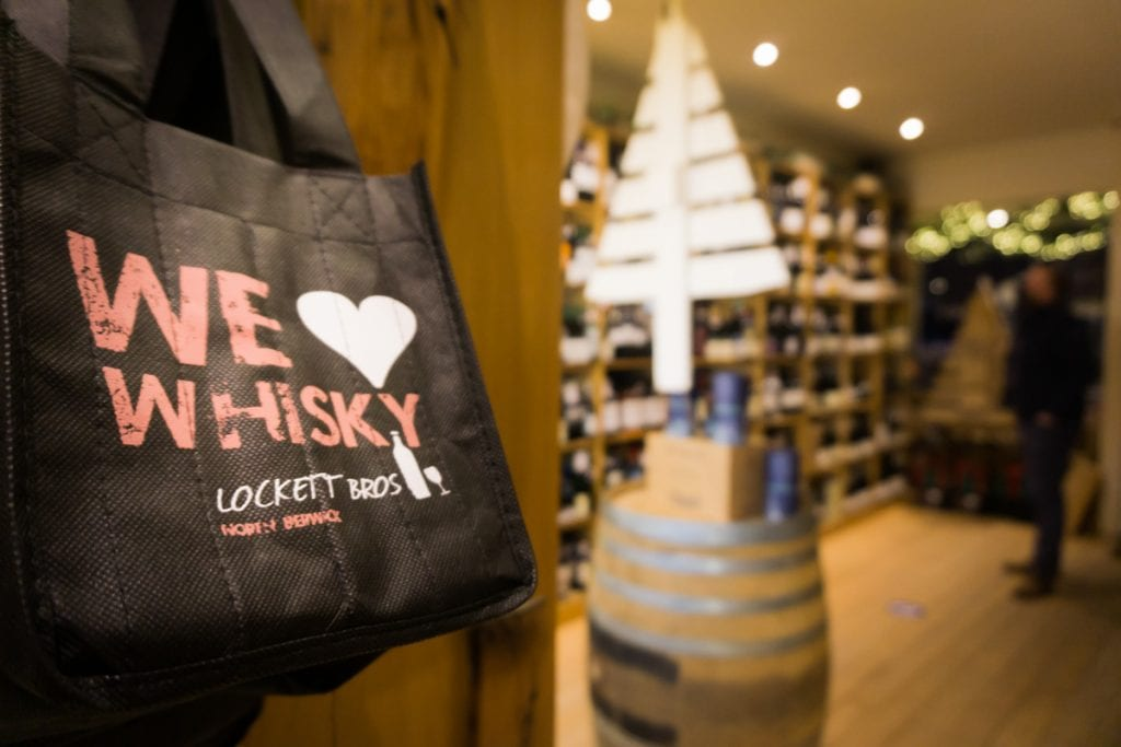 We Love Whisky bag hanging in bottle store