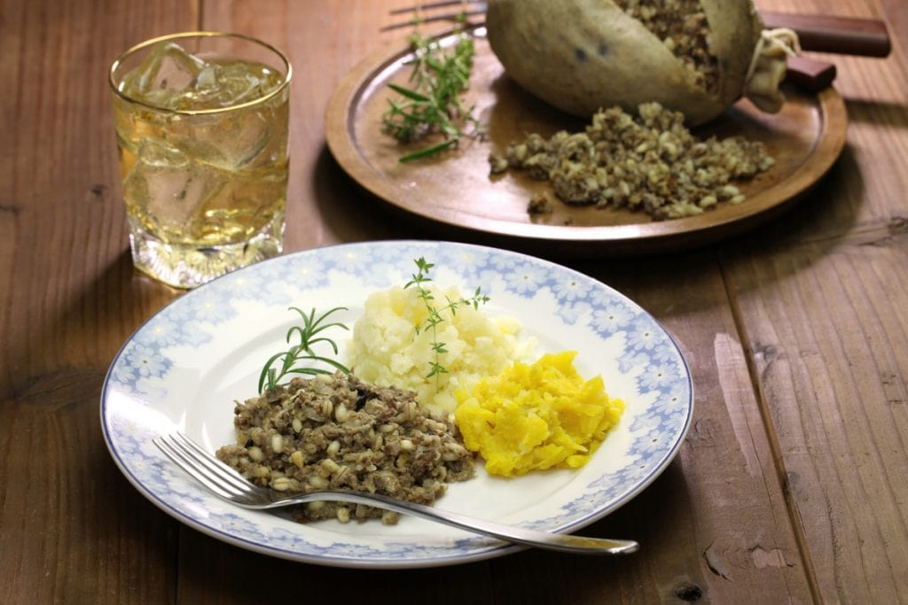 Haggis Neeps and Tatties on a plate with whisky beside for a Burns Supper Menu