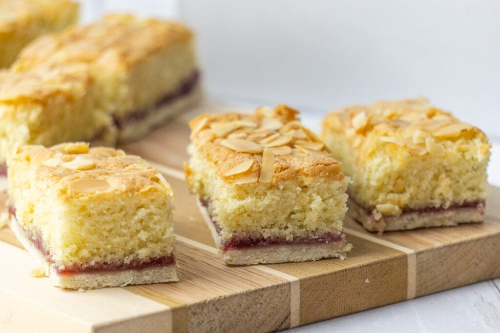 Almond Slice Recipe on a wooden board - A Bakewell Slice with pastry bottom, raspberry jam, and an almond sponge