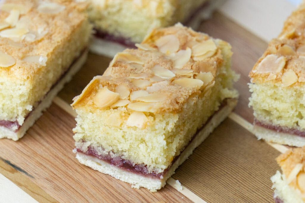 Almond Slice Recipe with slices on a wooden board - Pastry layer, topped with jam and almond sponge